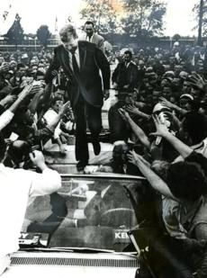 October 5, 1960: Presidential nominee Senator John F. Kennedy walks gingerly over the tops of automobiles when the press of people at Carbondale, IL, prevented his cavalcade from getting close to the speakers' stand.