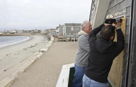 Mike MacLelland II and his father boarded up his winter rental cottage on Turner Road in Scituate Sunday.