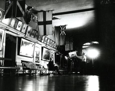 November 7, 1960: Presidential candidate John F. Kennedy sits alone in a room off the main auditorium at Faneuil Hall before making the final campaign speech  as the television technician from CBS sets up the camera. He was introduced by the candidate for Vice President, Senator Lyndon B. Johnson and began his speech at 11 p.m. He ended his remarks by saying,