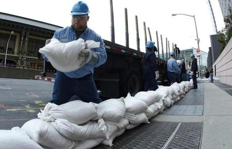 Con Edison workers placed sandbags to cover power vaults in New York.