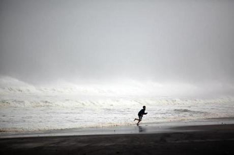 A young boy ran along Rockaway Beach in Queens.