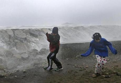 Youngsters ran as waves crashed against a seawall in Scituate.