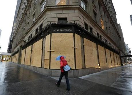 A woman walked past a boarded up Saks Fifth Avenue in New York.