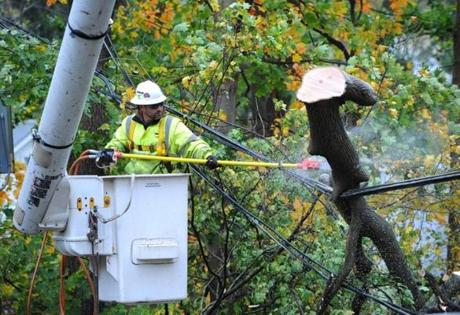 Matt Moran cut a fallen limb from a power line in Sea Clff, N.Y.