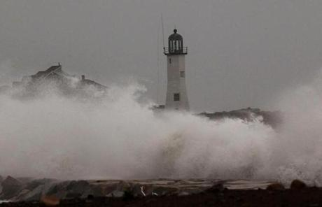 Waves crashed over a jetty in Scituate.