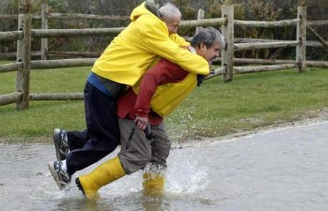 Chris Losordo carried his father Vin across flooded Menauhant Road in Falmouth.