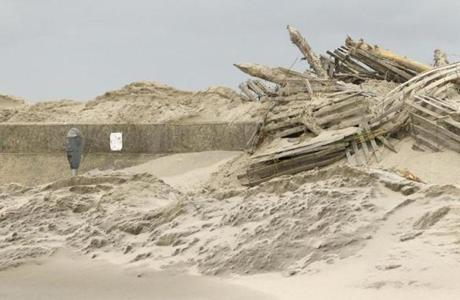 Sand and debris covered parking meters on the seawall along Beach Avenue in Cape May, N.J.