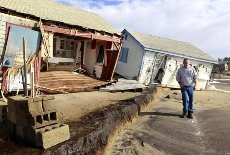 A man walked past cottages damaged by Sandy on Roy Carpenter's Beach in South Kingstown, R.I.