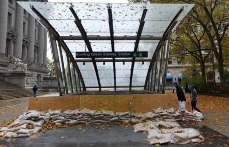 People peeked into the closed Bowling Green subway station after Hurricane Sandy hit in New York.