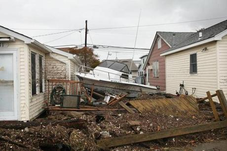 A boat washed up in the storm surge sat between houses in the Breezy Point neighborhood of Queens.