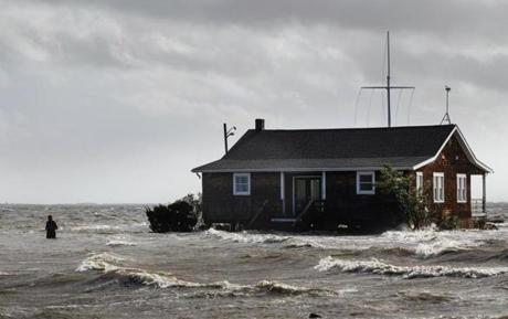 A man walked away from a building that has been surrounded by water in Bellport, N.Y.