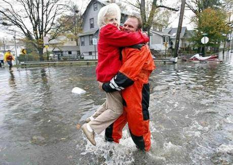 A rescuer carried an elderly resident in Little Ferry, N.J.