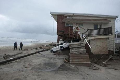 A damaged car sat in the remains of a house in the Rockaways section of New York.