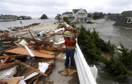 Brian Hajeski of Brick, N.J., looked at debris of a home that washed up on to the Mantoloking Bridge in Mantoloking, N.J.