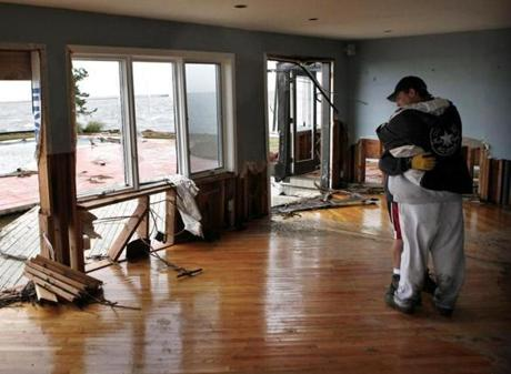 Johnny Adinolfi was comforted by neighbor John Vento, right, as he stood in  the living room of his damaged home in Massapequa, N.Y.