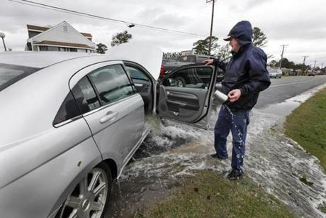Glenn Heartley watched floodwaters pour out of his car after it was pulled out of a creek in Chincoteague, Va., Tuesday.