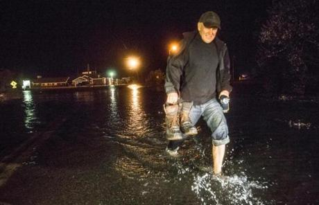 Mike Biszko waded through knee-deep water flooding Bridge Street in Westport, Mass., after checking on his home.