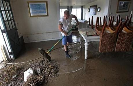 Jason Locke moved mud out of his mother's home near Gooseberry Point at Horseneck Beach in Westport.