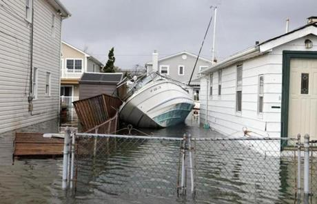 A boat was almost sideways between two flooded houses in Lindenhurst, N.Y.
