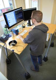 Jay Ciruolo works at his standing desk at CarGurus in Cambridge.