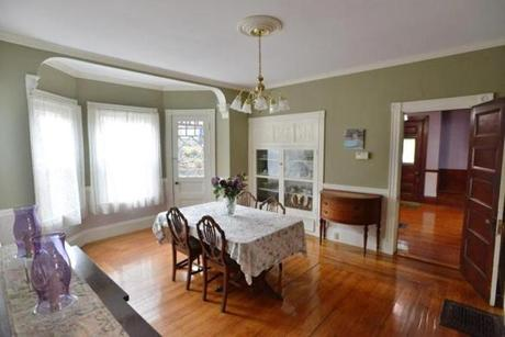 Bay windows allow light into the formal dining room. Floors are original hardwood.