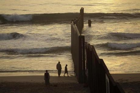 People at a beach next to the border fence separating Mexico from the US in Tijuana, Mexico.
