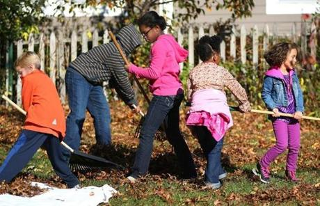 Dorchester-11/232012- Youngsters help rake leaves at the Dorchester Historical Society's grounds on Boston Street during an open house and farm fair . Globe staff photo by John Tlumacki (lmetro)