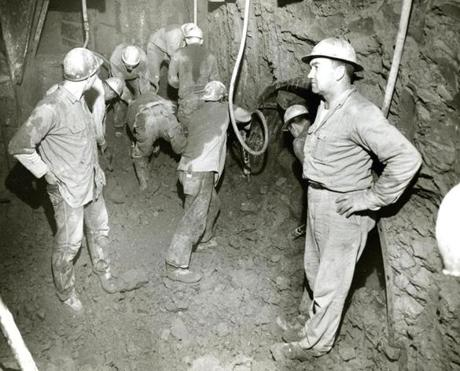 March 3 1961: This photo shows workmen as they exposed the pilot, 6 x 8 feet tunnel coming from Boston and the main tunnel coming from East Boston. The two tunnels met under North St. in Boston's North End. There was less than a half-inch variance from the plans on either side of the two tunnels. The foreman overseeing the breakthrough, on the right, was Ken Smith from Brighton.