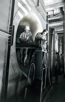 September 6 1961: The nine foot diameter of these powerful fans used for ventilation at the East Boston end of the new tunnel dwarfed project engineer Irving R. Huie (left) and Clyde H. Galbraith, coordinating field engineer for the equipment maker. The bank of three fans could move up to a million cubic feet of air per minute. The new Lt. William F. Callahan Jr. tunnel would open on November 11, 1961, the 40th anniversary of the birth of the late war hero. Only son of Massachusetts Turnpike Commissioner William F. Callahan, the lieutenant fell in action April 14 1945. His death occurred during an attack in the mountains of northern Italy, a few weeks before World War II ended.