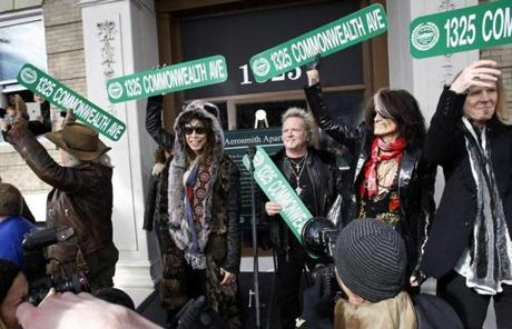 Band members Brad Whitford, Steven Tyler, Joey Kramer, Joe Perry, and Tom Hamilton held up street signs in front of their old apartment.