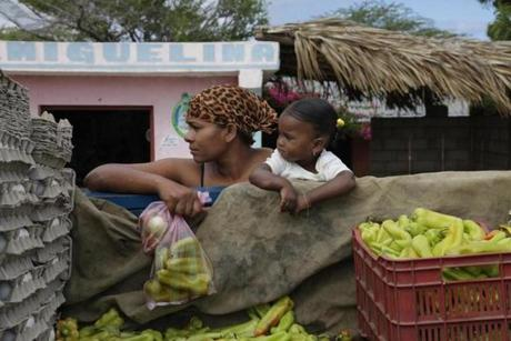 A mother and daughter buy vegetables off the truck in one of the small farming towns scattered across the uplands of Pedernales province.