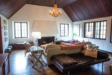 The great room has a fireplace, wood flooring, wood-planked ceiling, and textured plaster walls.