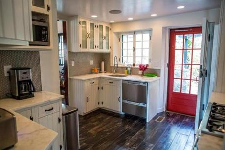 The updated kitchen boasts stainless-steel appliances, tile flooring, marble countertops, and penny-round ceramic backsplashes.