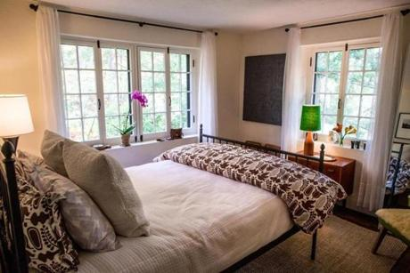 A first floor bedroom features wide windows.