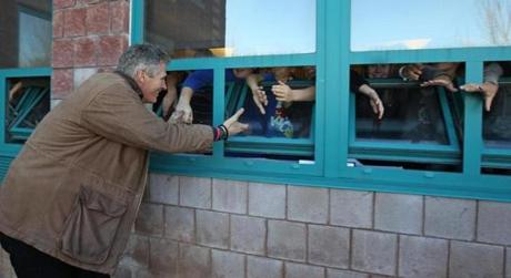 Eighth-graders at the Sullivan Middle School in Lowell held out their hands to shake with Senator Scott Brown as he asked the kids to tell their parents to vote for him. Nov. 6, 2012.