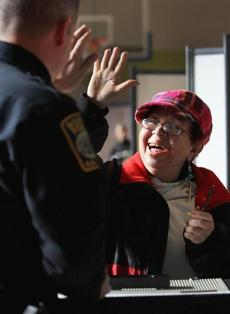 Milagros Pena high-fived Boston Police Officer Brendan Lyons after casting her ballot at Orchard Gardens in Dorchester.