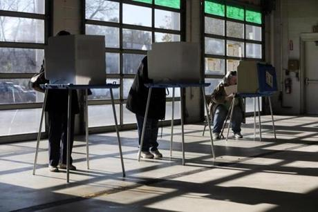Voters filled out their ballots in a vehicle storage bay at Armory Garage, an auto dealership in Albany, N.Y.