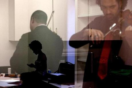 Melissa White reads a text message while Ilmar Gavilan (left) and Juan Miguel Hernandez prepared for their performance. The Harlem Quartet, part of New England Conservatory's highly competetive master quartet program, had a trying year looking for replacements for 2 of their members.