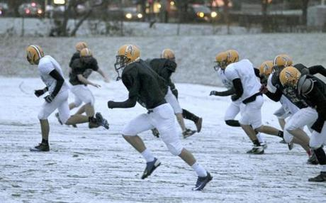 Members of the Arlington Catholic High School football team ran sprints in the snow Wednesday during practice on their Summer Street practice field.