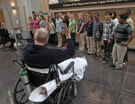 BOSTON MA.11/ 09 / 2012:Waves to the students from a wheelchair....The Executive Director of New England Kurn Hattin Homes for Children, Tom Fahner ( cq) has undergone a very serious cancer operation and is recovering well. Brigham and Womens Hospital in Boston has agreed to allow the school's select children's choir to perform for him in his hospital room at 1pm today. The choir director, Lisa Bianconi thought of this idea and pitched it to the hospital who just agreed to it this morning. Established in 1894, Kurn Hattin Homes for Children in Westminster, Vermont is a charitable home and school for boys and girls, ages 6-15, who are affected by tragedy, social or economic hardship, or other disruption in family life. Its mission: Kurn Hattin transforms the lives of children and their families forever. ( David L Ryan/Globe Staff Photo ) SECTION: METRO TOPIC stand alone photo