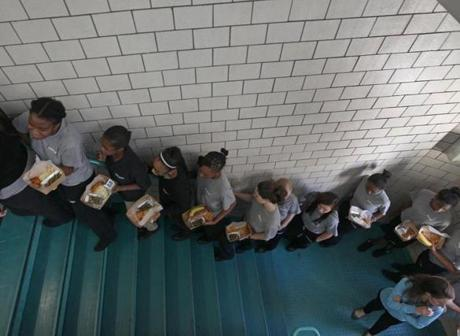 BOSTON MA.11/ 09 / 2012:Eight grade students returning from lunch walking up stairway with Teacher Christine Adamson ( cq) at UP Academy which was converted from the old Gavin Middle School into a charter school, Unlocking Potential has faced mounting criticism that it has been forcing out students who are flunking their classes or who are overly disruptive, as part of a plan to boost test scores. But data compiled by the School Department shows that students withdrew from Unlocking Potential's UP Academy at a rate lower than the average for middle schools in Boston. ( David L Ryan/Globe Staff Photo ) SECTION: METRO TOPIC 10upacademy