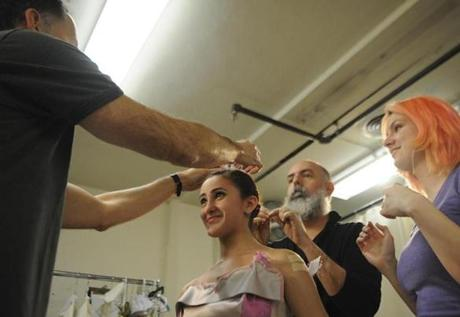Boston Ballet costume and set designer Robert Perdziola (left) fit dancer Alexandra Heier, 16, with a bow on her head, as Charles Heightchew, the manager of costumes and wardrobe for the ballet, and Lexxy Weglowski watched on June 5.