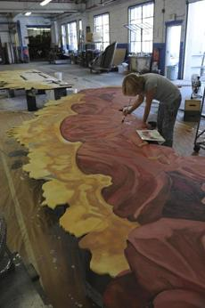 A scenic artist at the Mystic Scenic Studios, Inc in Norwood  worked on a backdrop for the new production on October 17.