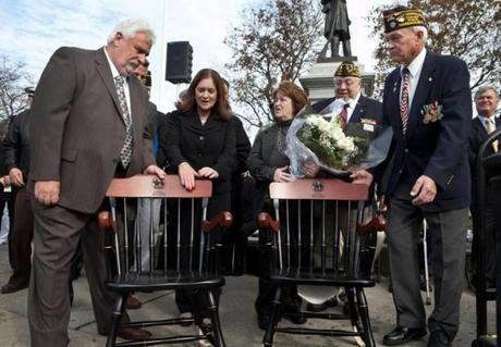 John Flaherty (left), a Woburn philanthropist who funded the building of the new Woburn War Memorial, and his wife Kathy Flaherty (third from left), receive a gift of chairs from the Friends of Woburn Veteran's Committee during the Veteran's Day ceremony on Woburn Common preceding the unveiling of the new War Memorial on Sunday. Kathy Lucero (second from left), and George Poole (right) presented the chairs to the Flaherty's.