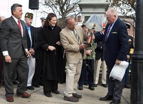 Robert Shure (center), designer of the new Woburn War Memorial, receives a gift of a lamp from the Friends of Woburn Veterans Committee during the Veterans Day ceremony on Woburn Common preceding the unveiling of the new War Memorial on Sunday. Mike McDounough (right) presented the lamp to Shure.