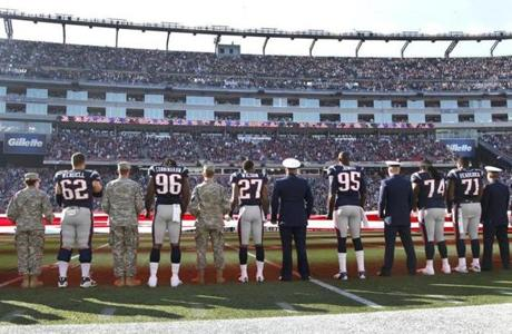 Patriots players lined up with service members for the national anthem prior to playing the Bills.