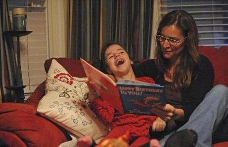 Cathy Jerome reads her daughter a book Sydni received for her birthday at their South Boston home.