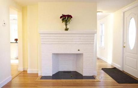 The living room has a brick fireplace painted white. Flooring throughout the house is the original oak, refinished.