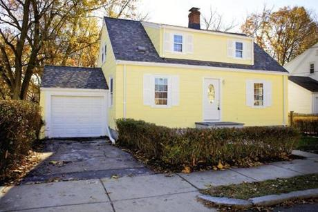 This yellow Cape with a full dormer sits on a dead-end street lined with homes of similar design.