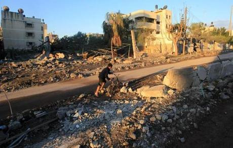 A Palestinian boy pushed his bicycle through the rubble Thursday in an area that had been targeted by an Israeli airstrike on Gaza City.